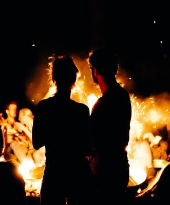 para patrzy na ognisko, które symbolizuje namiętność w ich związku
